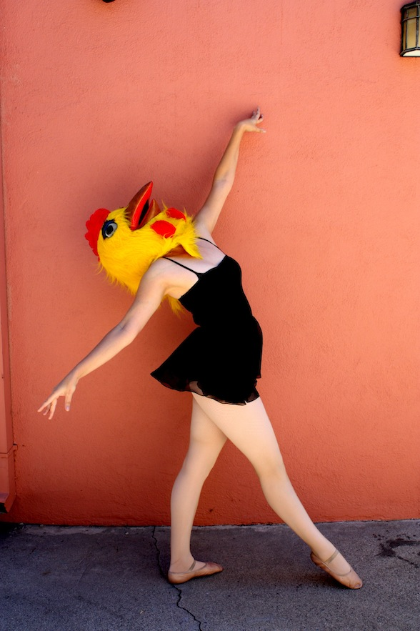 IMAGE The Adult Beginner poses in front of an orange wall wearing a large chicken head. IMAGE