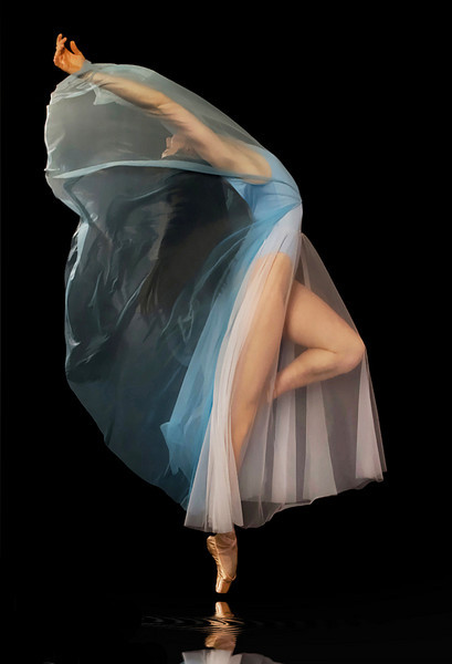 IMAGE A ballet dancer draped in a blue and white chiffon dress arches her back as sheer fabric covers her face and arms. IMAGE