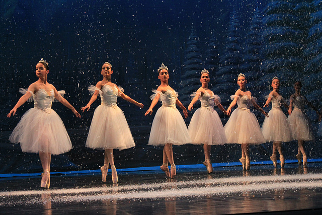 Dancers onstage in white tutus for Nutcracker snow scene