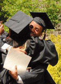 IMAGE Roger Lee in cap and gown, hugs a fellow graduate. IMAGE