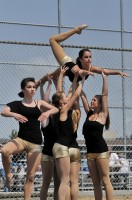 Photo of four dancers lifting another overhead as if in flight