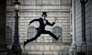 A dapper skeleton-faced man leaps across a street in Munich