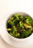 A white bowl contains broccoli and vegetables
