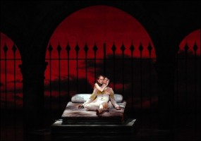 IMAGE Photo by Michael Seamans - Dancers: Larissa Ponomarenko and Nelson Madrigal (Boston Ballet) - Romeo and Juliet embrace on a bed before a red backdrop. IMAGE