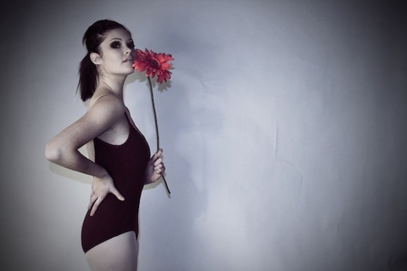 A dancer in leotard and tights holds a single red flower.