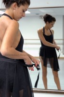 IMAGE A dancer ties her black ballet skirt as she stands before the studio mirror. IMAGE