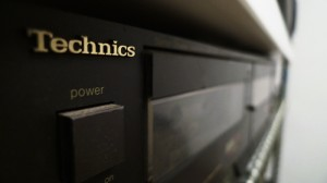 IMAGE Close visual of the power button and cassette deck of a Technics music stereo component. IMAGE