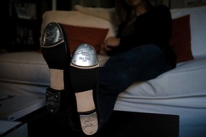 IMAGE Woman sits on a couch, displaying her new Capezio tap shoes. IMAGE