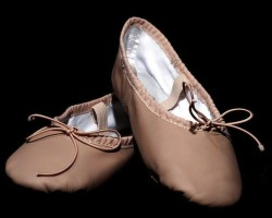 IMAGE Empty pair of child's ballet shoes displayed against a black background. IMAGE