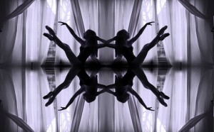 IMAGE A ballet dancer balances on her pelvis against a veiled window. On a reflective surface with a reversed image, there appears to be four of her. IMAGE