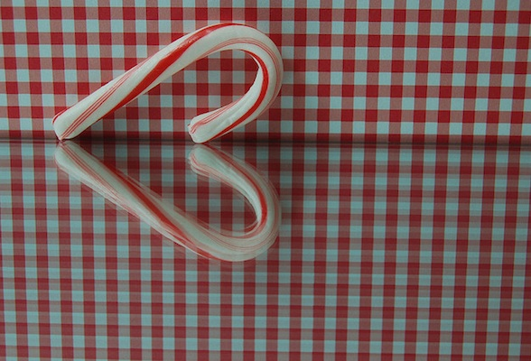 IMAGE A candy cane's tabletop reflection forms a heart. IMAGE