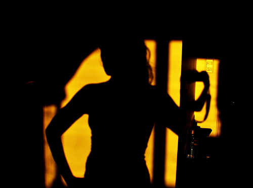 IMAGE A woman stands in darkness. Yellow light shines behind. IMAGE