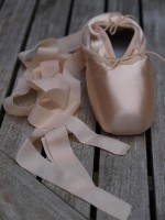 New pointe shoes with ribbons curling beside