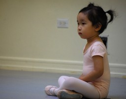 A young dancer in pink sits cross-legged with hands in her lap.