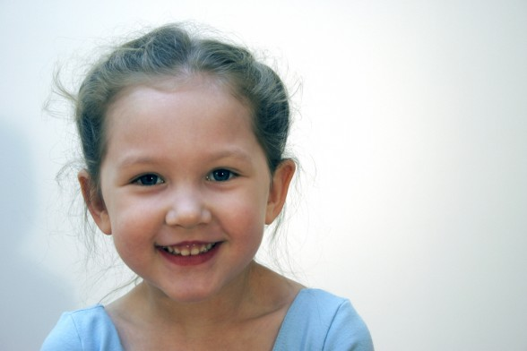 Tiny dancer in a light blue leotard with whispy hair and a big smile.