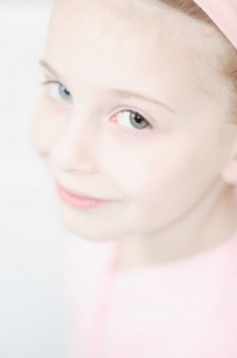 Portrait of a fair-haired young ballet dancer in pink leoard and headband