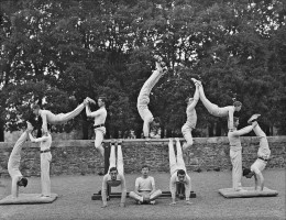 A group of 12 'gym class' participants create an architectural-looking pose for the camera in this vintage black and white photograph.