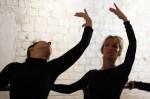 Adult ballet students perform cambré at the barre.