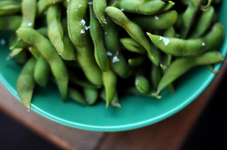 Edamame sprinked with salt and sitting in a green bowl.