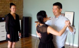 A wedding couple dance as teacher, Szewai Lee looks on.