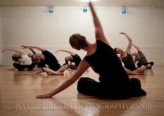 Class of dancers sitting, stretching side. Photo by Savage Rose Photography