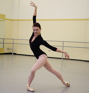 A ballet dancer performs and poses in the studio