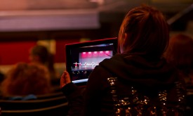 A dance mom captures her performing child on an ipad