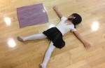 A young dancer flat on the floor like her scarf.