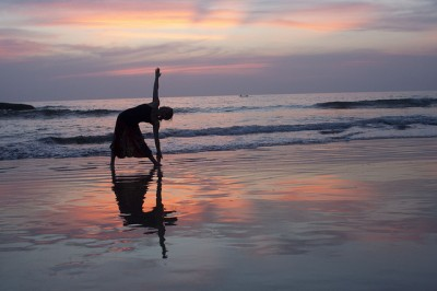 Woman practicing yoga on beach
