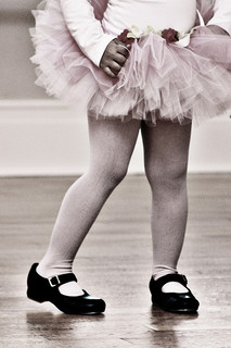 The legs of a child in tutu and tap shoes