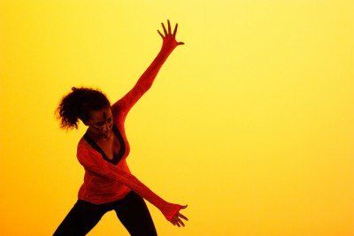 A dancer in red spreads arms on a yellow stage