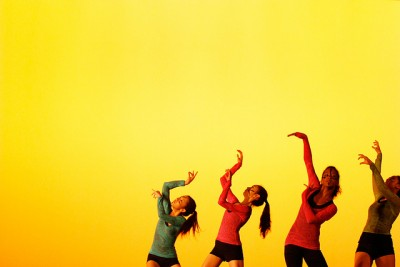 Four teen dancers lift their arms