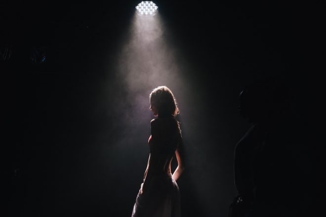 a woman stands in a spotlight