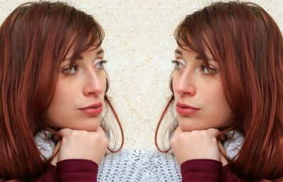 A woman stares judgmentally at her own image.