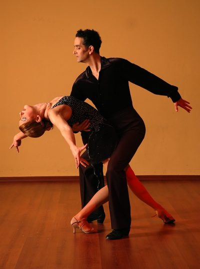 A male dancer dips a female ballroom dancer.