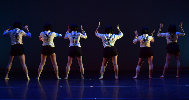 Six dancers in white shirts with black suspenders face upstage.