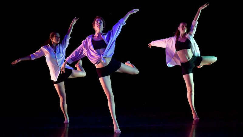 Three dancers in loose tops over black basics.