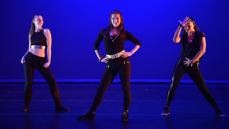 Three dancers in black against a blue backdrop