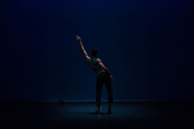 A dancer reaches his arm on a dark stage