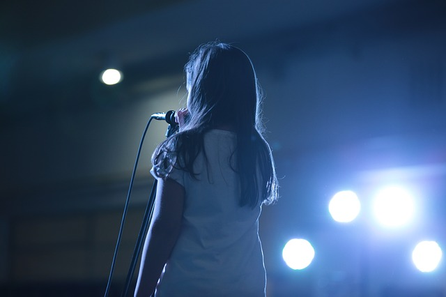 Girl singing on stage into a microphone